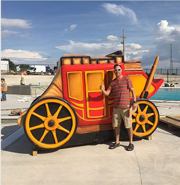Guy with sunglasses giving the thumbs up standing in front of a replica stagecoach at the water park